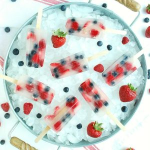 Colorful berry and coconut water popsicles lay in a bucket of ice