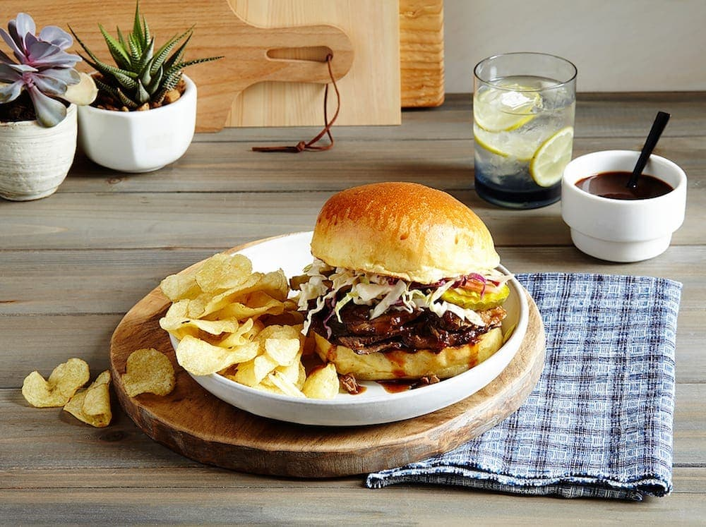 Slow Cooker Brisket Sandwich on table , white plate and board, blue napkin