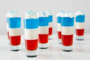 Layered red, white and blue jello shots with whipped cream and blue sprinkles
