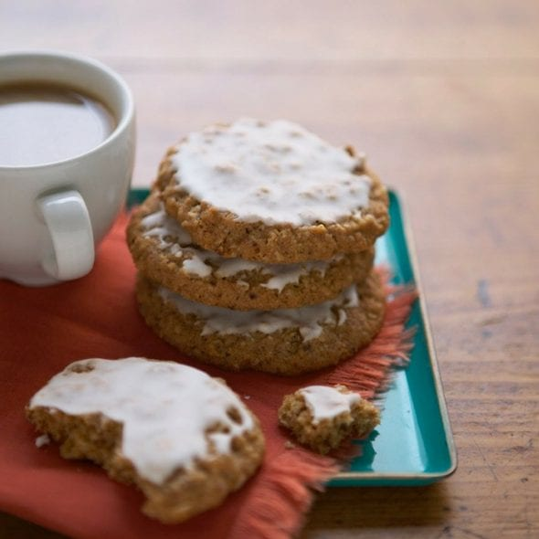 Classic Iced Oatmeal Cookies on orange napkin and turquoise plate w coffee