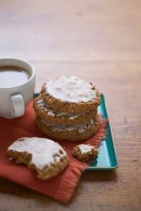 Classic Iced Oatmeal Cookies on teal plate with coffee