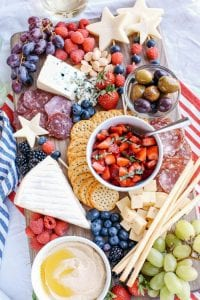 Decadent cheeseboard with strawberry salsa, blueberries, mozzarella stars and creamy hummus