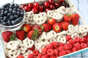 Fresh red fruit and white covered pretzels are arranged in an American flag pattern with blueberries in the corner for fun 4th of July food shared by Tara Teaspoon.
