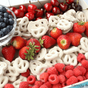 Fresh red fruit and white covered pretzels are arranged in an American flag pattern