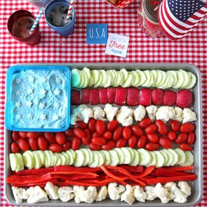Colorful veggies arranged in an American flag pattern with blue dip