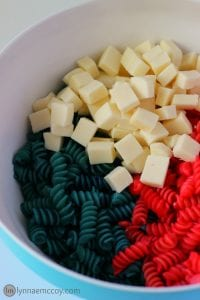Red and blue Rotini with cubes of mozzarella cheese cubes in a bowl