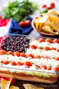 7 layer dip arranged in an American flag pattern with tomatoes, cheese and black beans