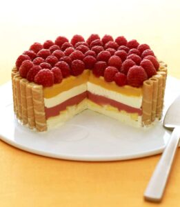 layered icebox cake with raspberries and mangos with slice missing