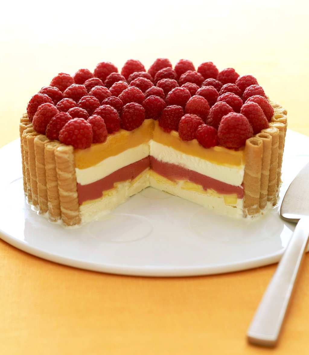 Fruit and Cream Icebox Cake with Mango and Raspberries on white plate and yellow linen with piece cut out