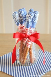 Red, white and blue dipped stick pretzels stand in a jar by an American Flag