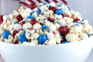 Caramel coated popcorn is mixed in with M&Ms, marshmallows ad sprinkles in a bowl with an American flag make great 4th of July food shared by Tara Teaspoon.