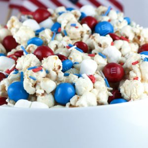 Caramel coated popcorn is mixed in with M&Ms, marshmallows ad sprinkles in a bowl