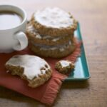 Iced Oatmeal Cookies on teal platter with coffee
