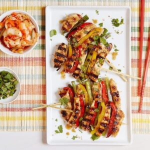 grilled Korean BBQ Chicken with bowls of toppings and red chopsticks