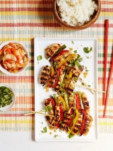 grilled Korean BBQ Chicken with bowls of toppings and white rice