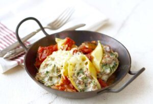 Easy Sausage Stuffed Shells in small metal wok pan with handles