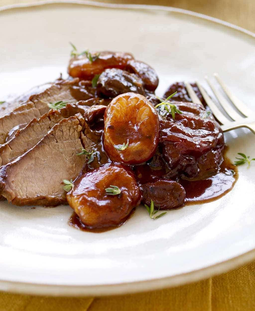 Brisket with Fruit and Wine Sauce on white place - close crop.