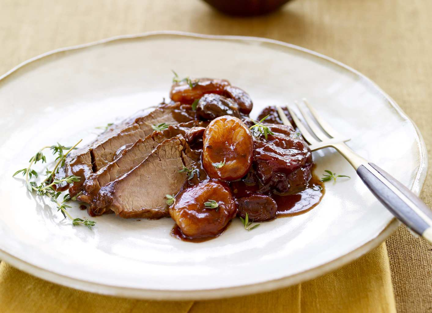 Slow Cooker Brisket with Fruit and Wine Sauce on white plate with gold background