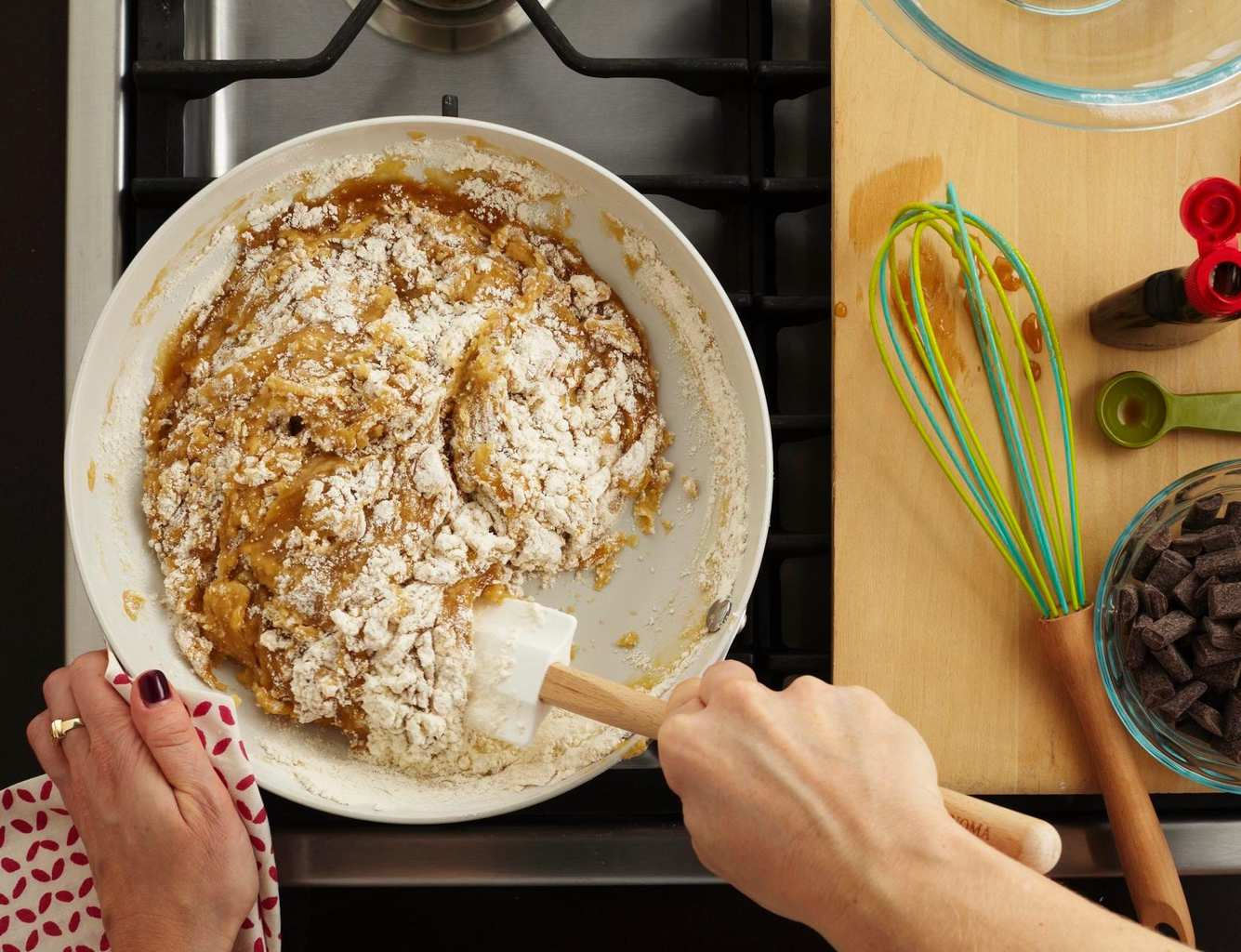 An overhead view of chocolate chip cookie dough being stirred together in a skillet.