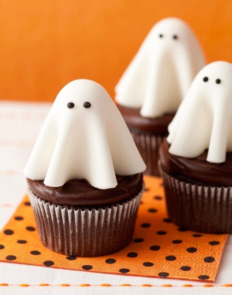 fondant ghosts with chocolate eyes on top of cupcakes