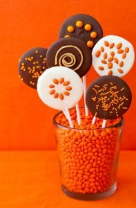 various Halloween Lollipops in cup with orange candies on orange surface and background