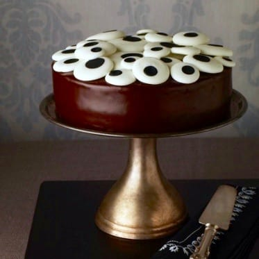 chocolate ganache cake with eyeball candy on top on gold cake plate