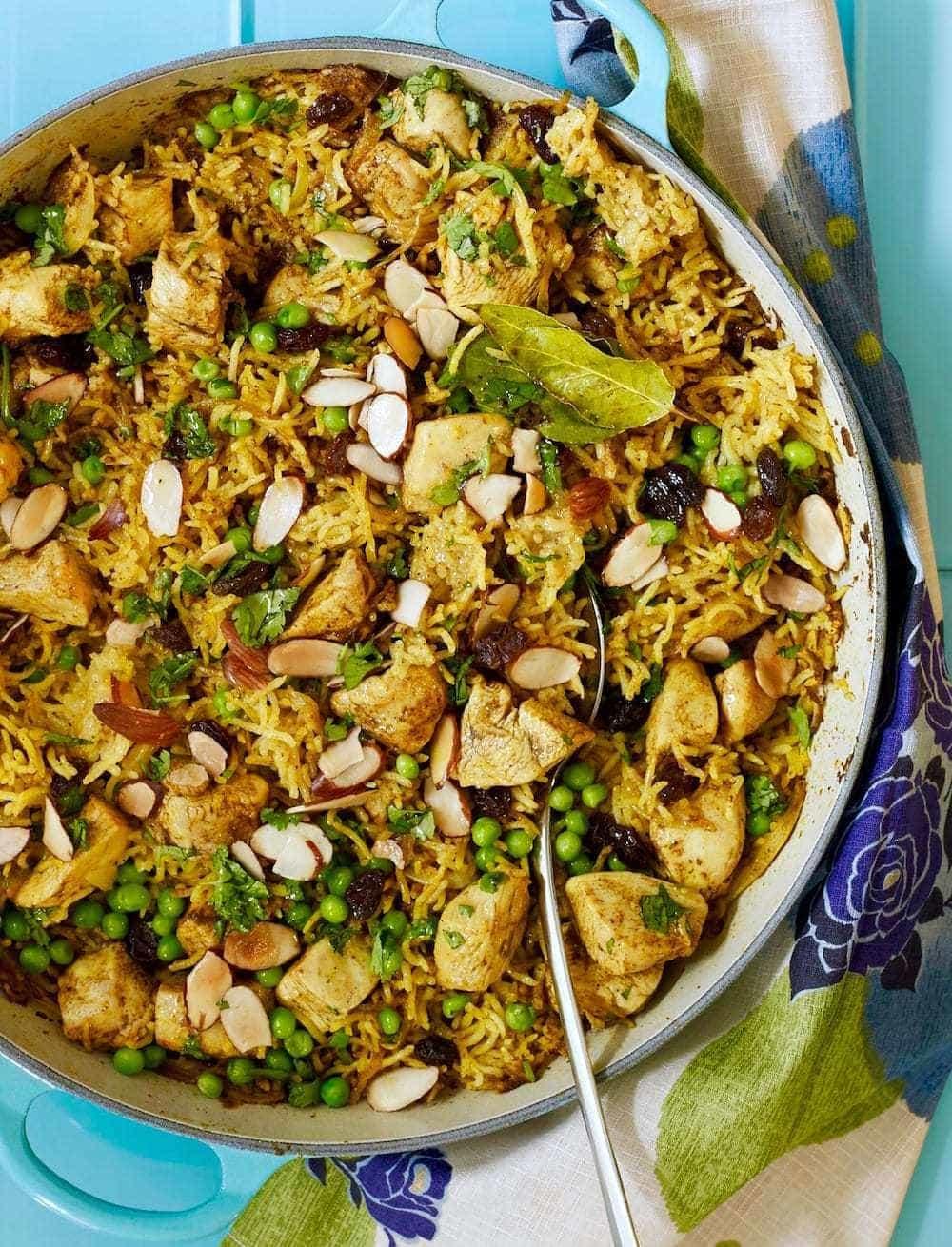 Chicken Biryani in a le creuset casserole on blue surface