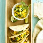fish tacos with mango and avocado salsa on a blue table