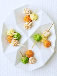 mini ice cream pops with orange, yellow and green candy sprinkles on white platter