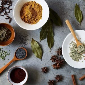 Spices in bowl and spoons on surface