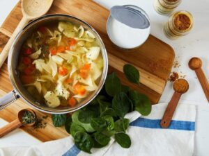 Chicken noodle soup with baby spinach leave on cutting board