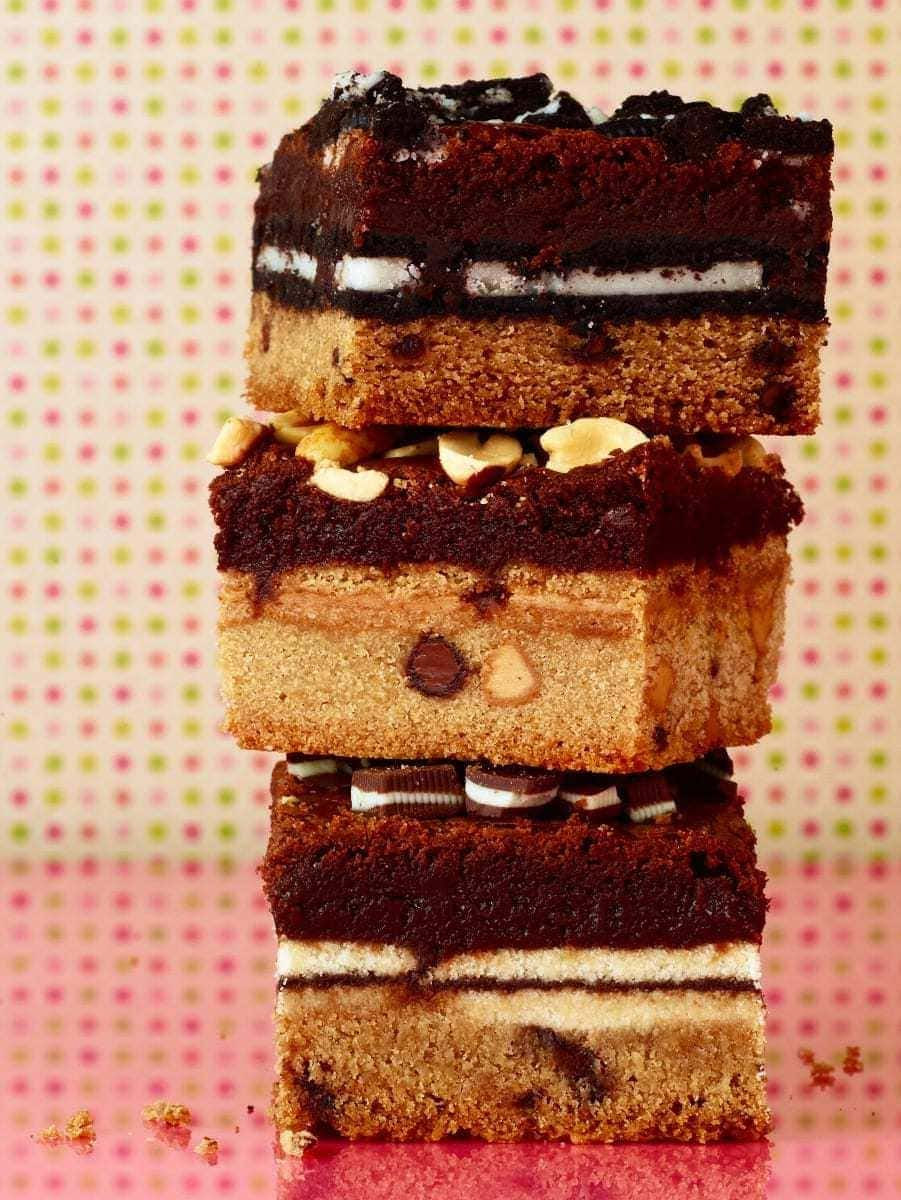 The ultimate cookie stuffed brownies squares stacked on pink surface