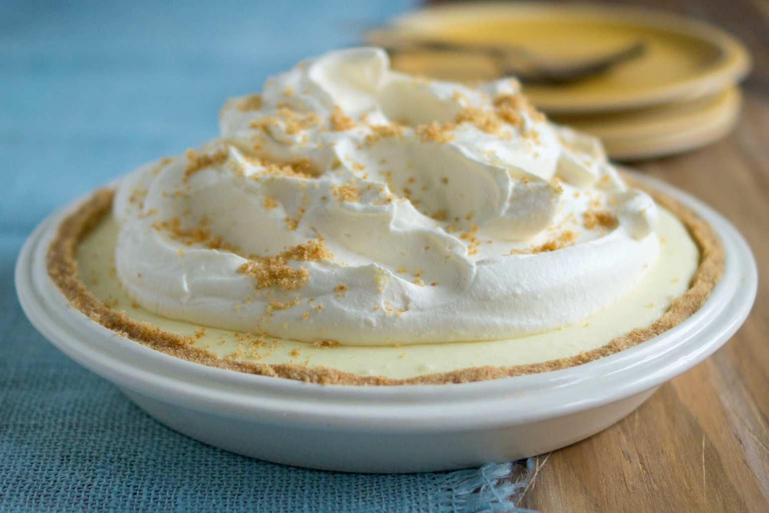 Delicious no-bake lemon icebox pie on blue placemat in white pie pan