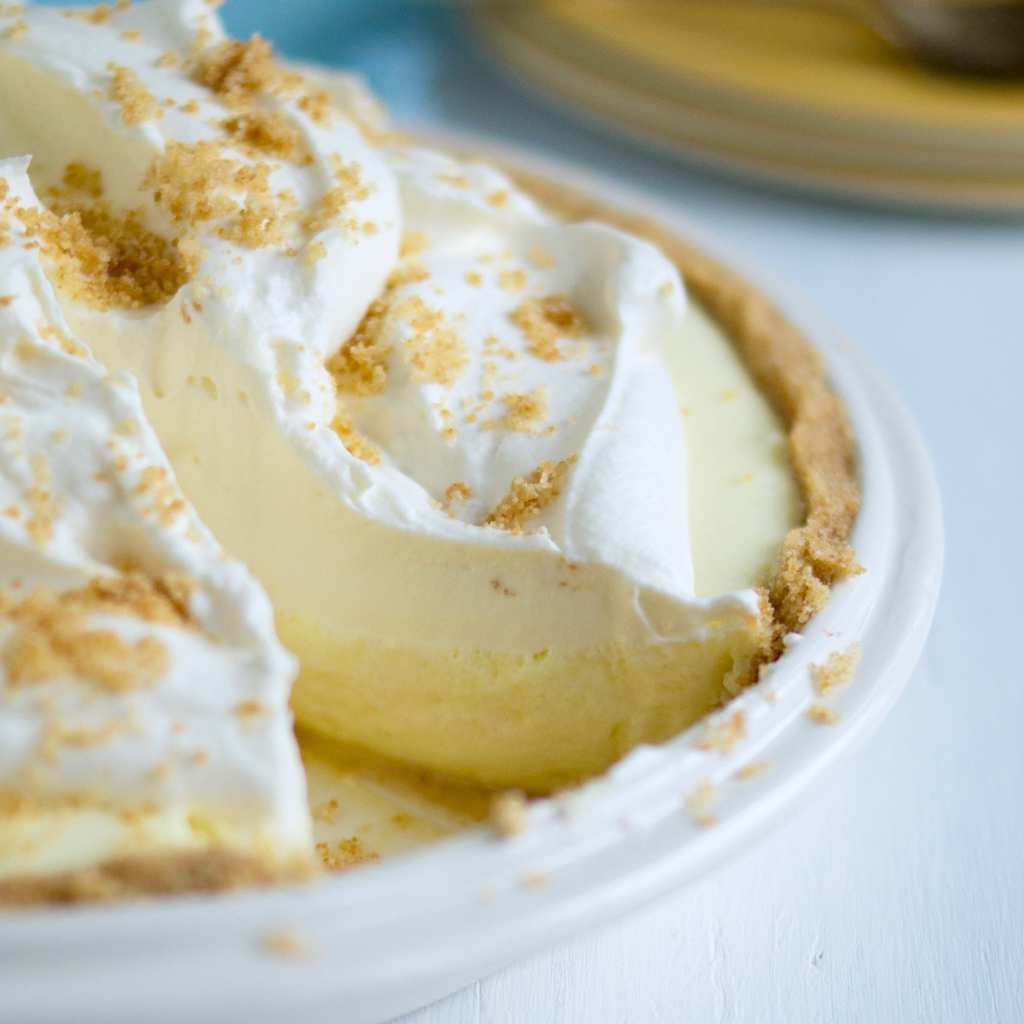 No-bake lemon pie in white pie pan with slice removed