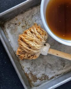 bbq mop suace with mop laying in aluminum tray