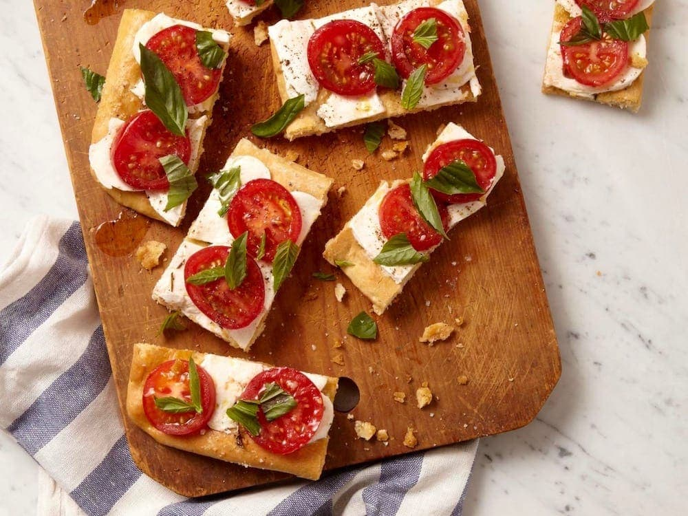 Caprese Focaccia cut on board with blue striped towel