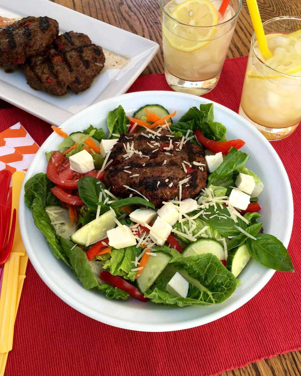 Grilled Italian bunless burgers in white bowl w red placemat and lemonade