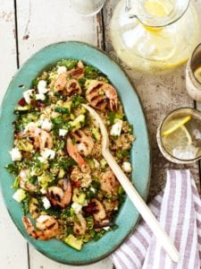 Grilled shrimp with zucchini and couscous on a wood table