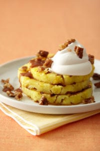Grilled Pineapple Praline stacked on white plate with whipped cream