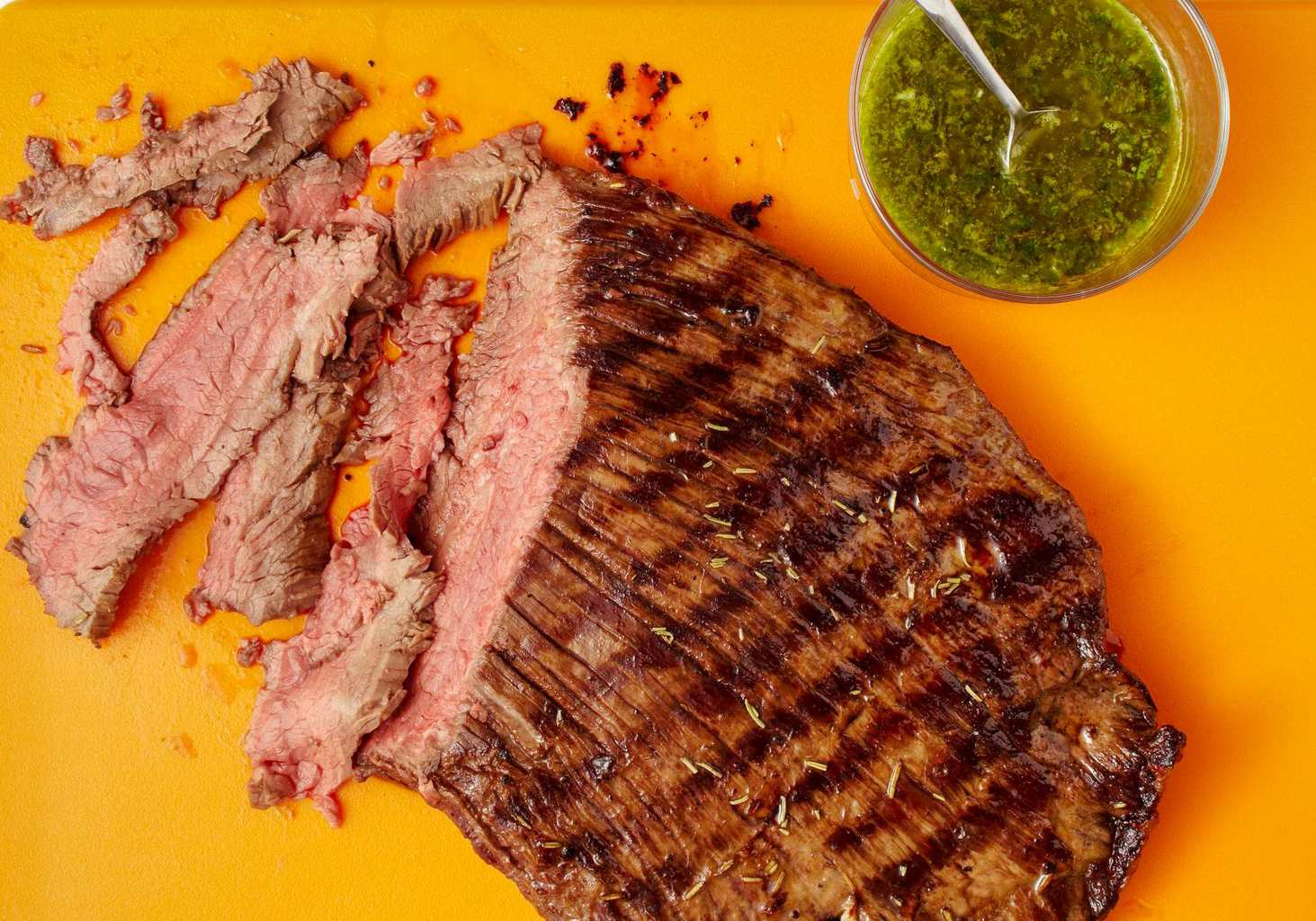 sliced grilled flank steak with salsa verde