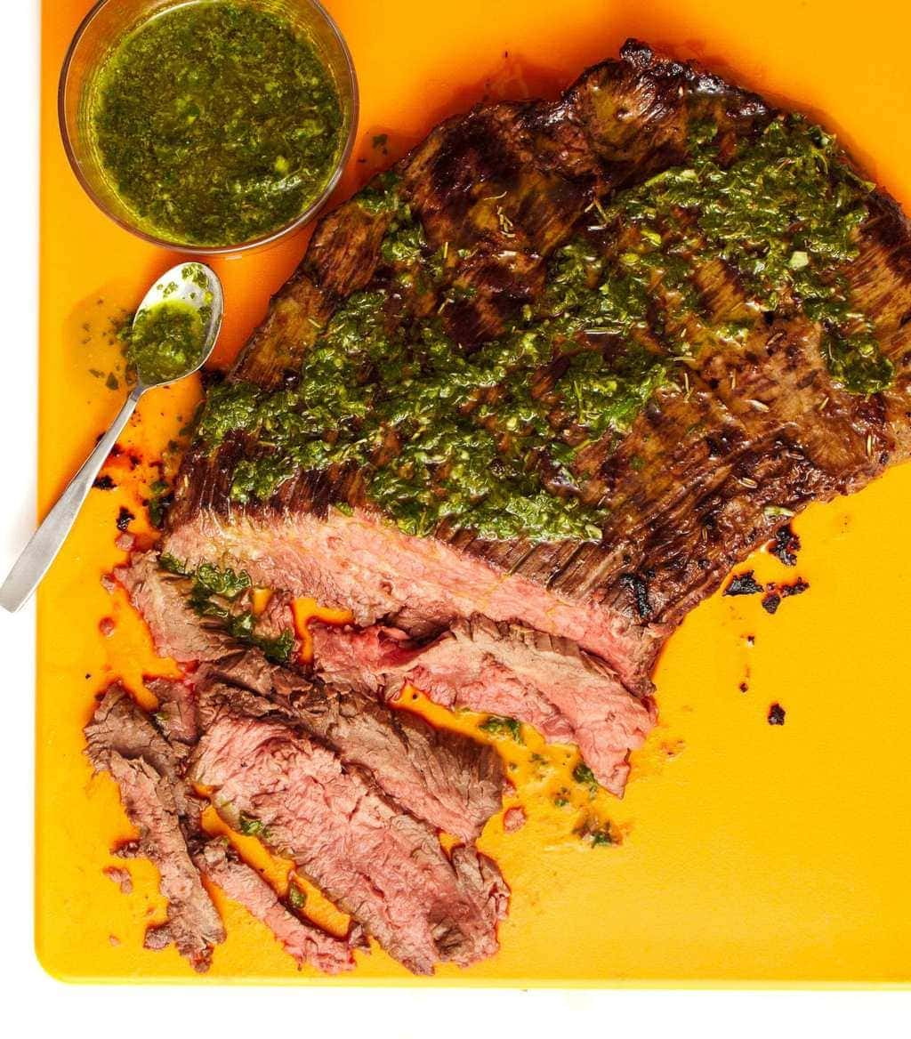 grilled flank steak on a yellow cutting board with salsa verde