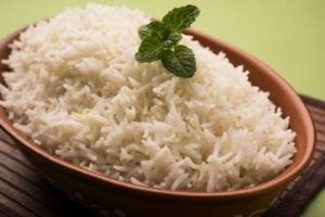 white rice in brown bowl with green garnish