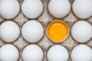 stock photo of eggs in egg carton adn one egg is showing the yolk