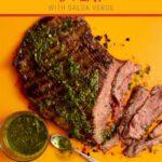 Grilled flank steak and green salsa on orange board