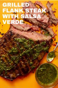 grilled flank steak with salsa verde on cutting board