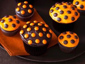 close up of halloween cupcakes with orange and brown frosting