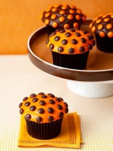 halloween cupcakes on a cake stand with orange background
