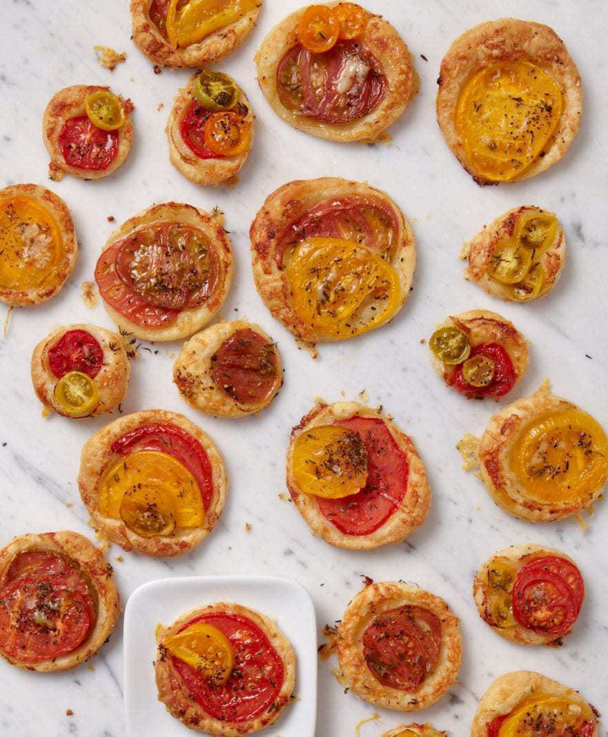 tomato tarts with gruyere cheese and thyme on marble and small white plate