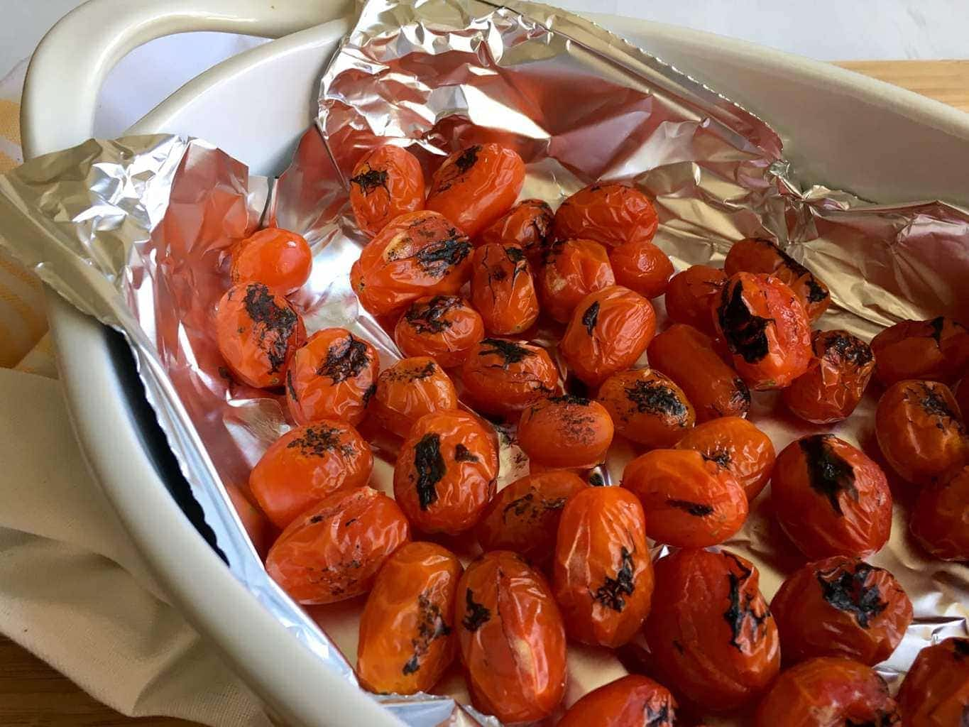 charred tomatoes in a dish for ravioli bake