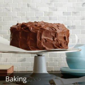 cake with chocolate frosting on whte cake stand in kitchen